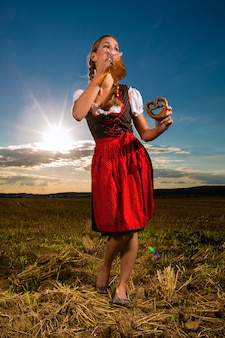 Frau mit tracht, bier und brezel in bayern