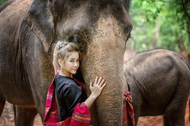 Frau mit traditionellem thailändischem kleid umarmt ihren elefanten am elefantendorf, surin, thailand