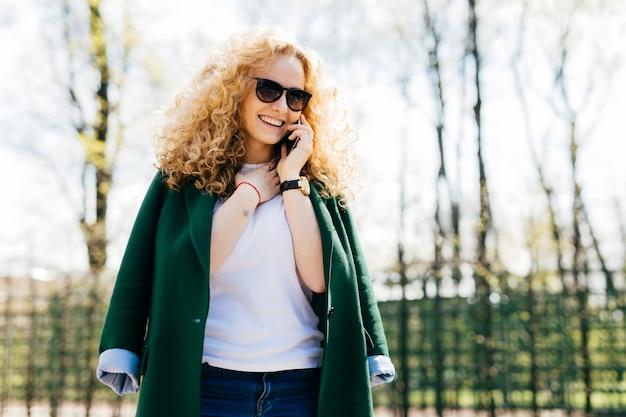 Frau mit tragender sonnenbrille und grüner jacke des gelockten blonden haares sprechend auf ihrem mobiltelefon