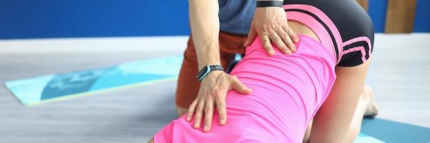 Frau mit trainer führt dehnübungen in nahaufnahme durch