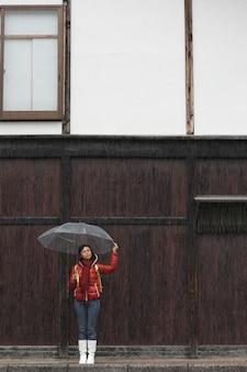 Frau mit transparentem regenschirm in regnerischem mit hölzerner wand. regenzeit-konzept.