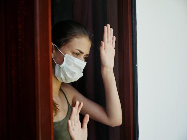 Frau mit traurigem gesichtsausdruck in medizinischer maske, die aus dem sperrfenster schaut