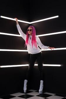 Frau mit trendigen rosa zöpfen in weißlicht. tragbares digitales innovationstechnologiekonzept für virtuelle augmented reality reality