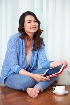 Frau mit trinkendem kaffee der digitalen tablette