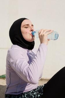 Frau mit trinkwasser der purpurroten jacke