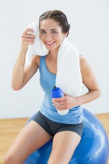Frau mit tuch um den hals und wasserflasche, die auf übungsball sitzen
