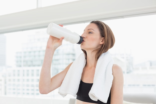 Frau mit tuch um trinkwasser des halses im eignungsstudio