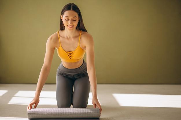 Frau mit übendem yoga der yogamatte