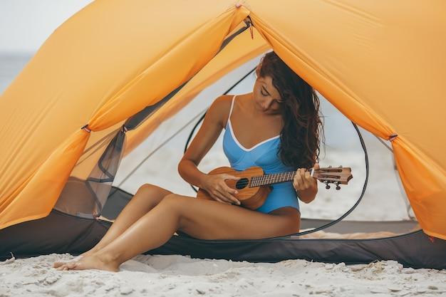 Frau mit ukulele am strand unter einem orangefarbenen zelt