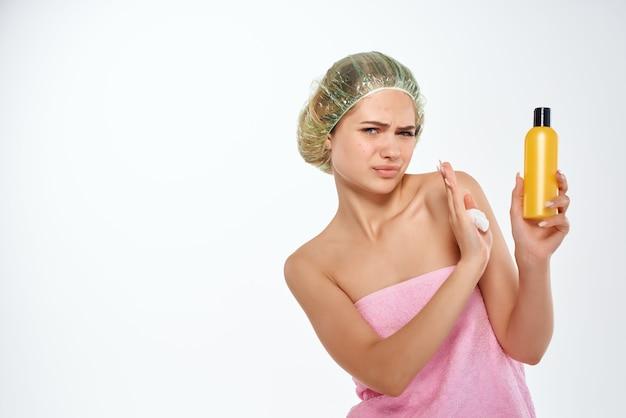 Frau mit unglücklichem gesichtsausdruck in rosa handtuchlotion hautpflege