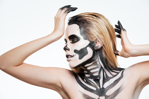 Frau mit verängstigtem halloween-make-up, die auf weißem hintergrund steht und posiert