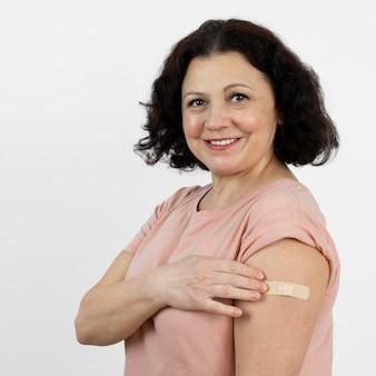 Frau mit verband am arm nach impfung