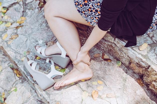 Frau mit verletztem fuß und draußen leiden an den beinschmerz wegen des unbequemen schuhes