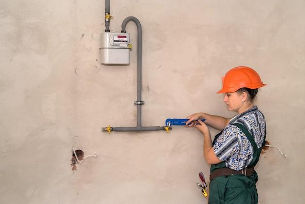 Frau mit verstellbarem schlüssel, der krane im sanitär repariert