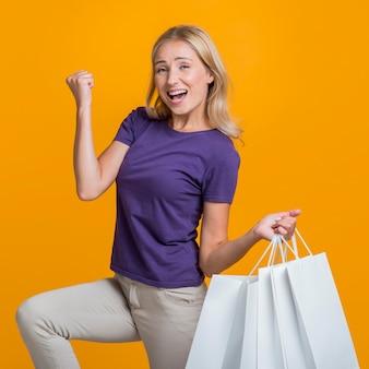 Frau mit vielen einkaufstaschen, die über ihren verkaufseinkaufsbummel glücklich sind