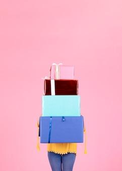 Frau mit vielen geschenkboxen, die ihr gesicht gegen rosa hintergrund abdecken