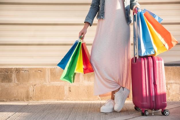 Frau mit vielen hellen einkaufstaschen und koffer