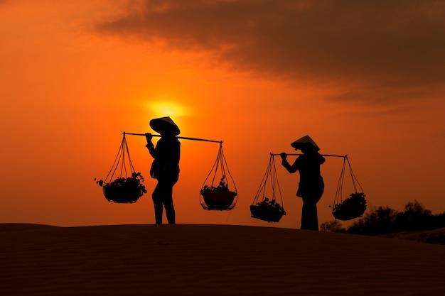 Frau mit vietnam-kulturtrachtenkleid auf sandune während des sonnenuntergangs