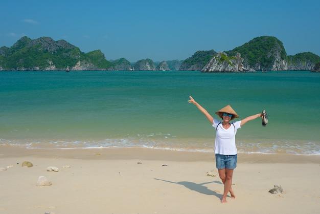 Frau mit vietnamesischem hut auf monkey island-strand cat ba halong bay, vietnam.