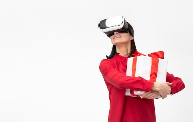 Frau mit virtueller realität headset hält geschenkbox