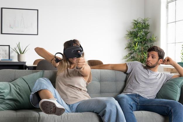 Frau mit vr-brille auf couch mittlerer aufnahme