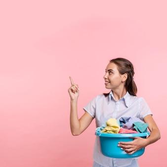 Frau mit wäschebecken oben zeigend