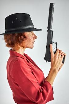 Frau mit waffe gegen weiß. detektiv rothaarige frau im schwarzen hut suchen