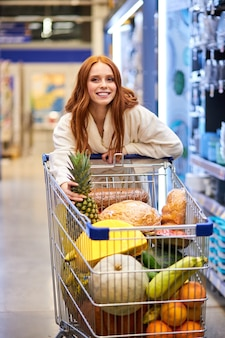 Frau mit wagen voller gemüse und obst im laden, zu fuß in der haushaltswarenabteilung, frau im bademantel genießen das einkaufen allein
