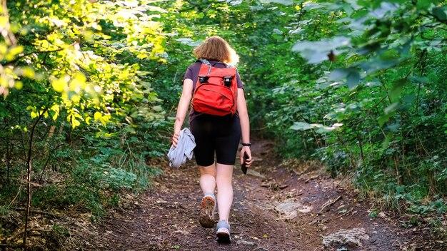 Frau mit wanderrucksack auf einem waldweg
