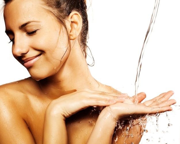 Frau mit wassertropfen auf ihrem reinen gesicht