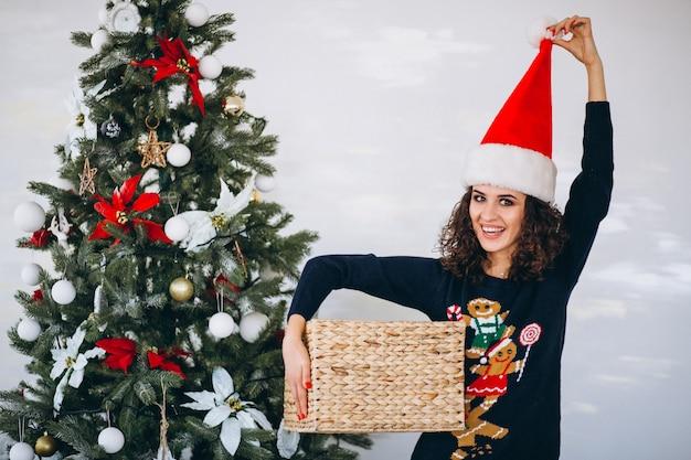 Frau mit weihnachtsgeschenk durch weihnachtsbaum