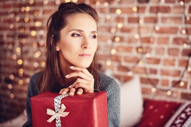 Frau mit weihnachtsgeschenk träumt