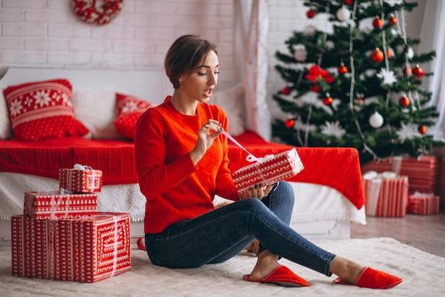 Frau mit weihnachtsgeschenken durch weihnachtsbaum
