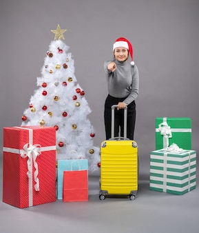 Frau mit weihnachtsmann-hut mit gepäck neben weihnachtsbaum