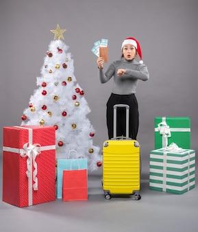 Frau mit weihnachtsmannmütze mit gepäck neben dem weihnachtsbaum