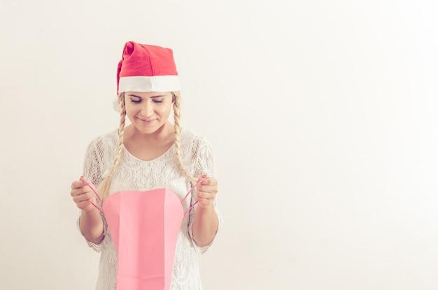 Frau mit weihnachtsmütze, die das weihnachtsgeschenk öffnet
