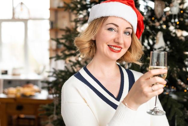 Frau mit weihnachtsmütze, die ein champagnerglas mit kopienraum hält