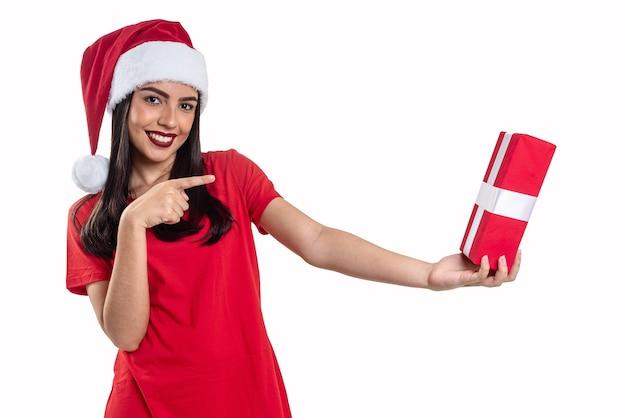 Frau mit weihnachtsmütze, die ein geschenk hält, lokalisiert auf weißem hintergrund.