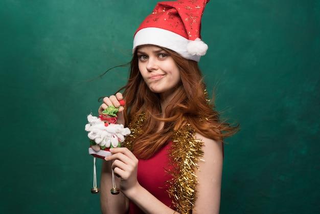 Frau mit weihnachtsmütze, die gegen die dunkelgrüne wand aufwirft