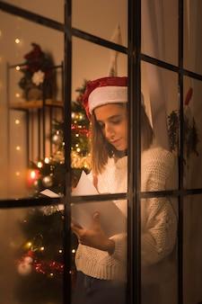 Frau mit weihnachtsmütze durch fenster, das buch an weihnachten hält und liest