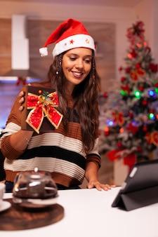 Frau mit weihnachtsmütze mit videoanruf-konferenz