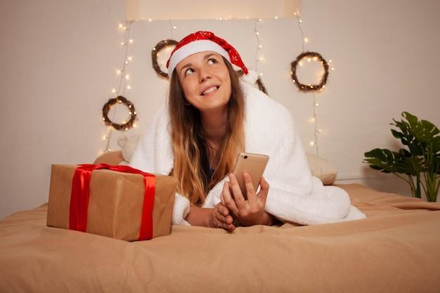 Frau mit weihnachtsmütze und geschenkbox auf bett. weihnachtsdekoration.