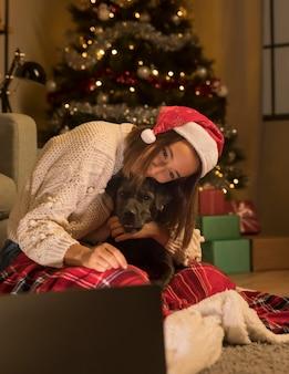 Frau mit weihnachtsmütze und ihrem hund an weihnachten, der laptop betrachtet