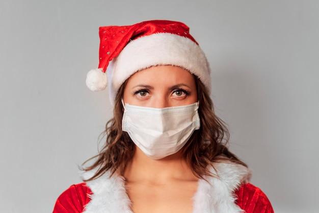 Frau mit weihnachtsmütze und medizinischer gesichtsmaske, grauer hintergrund