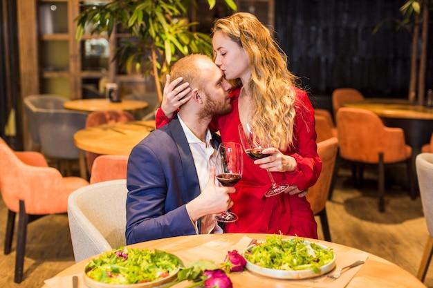 Frau mit weinglas mann auf stirn küssend