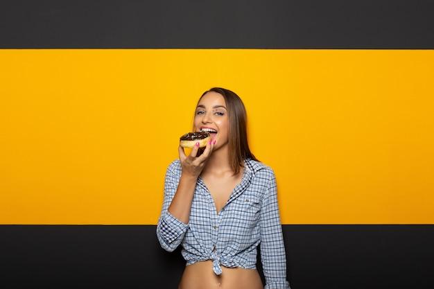 Frau mit weißem hellem lächeln geschmackvollen donut essend.