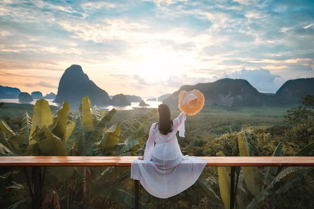 Frau mit weißem kleid sitzt auf bank vor schönem wald