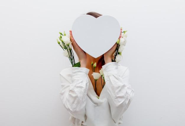 Frau mit weißen rosen, die eine herzform-geschenkbox halten.