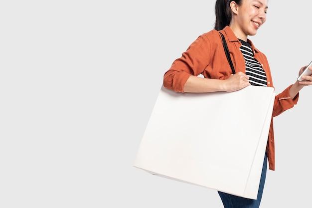 Frau mit weißer einkaufstasche mit designfläche
