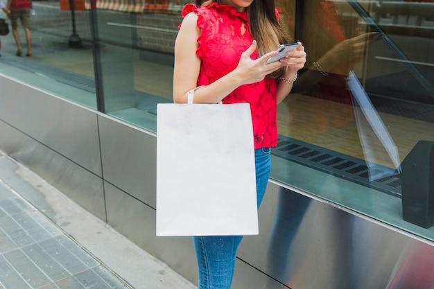 Frau mit weißer einkaufstasche und telefon